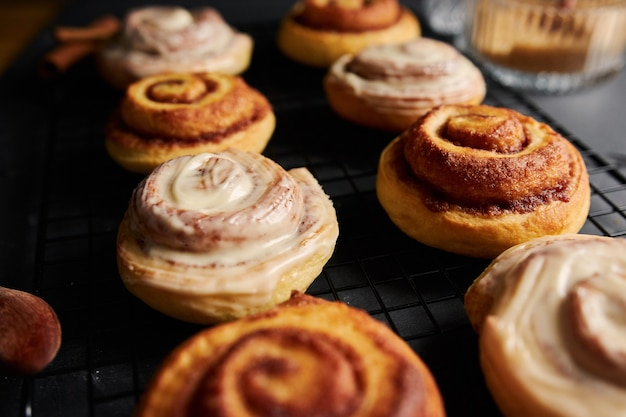Beautiful shot of delicious cinnamon rolls with white glaze on a black table