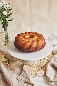 Beautiful shot of a delicious ring cake put on a white plate and a white flower near it