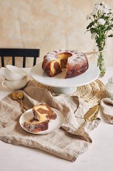 Bella ripresa di una deliziosa torta ad anelli posta su un piatto bianco e un fiore bianco vicino