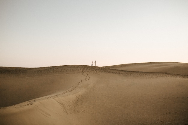 Beautiful shot of a desert hill with two females holding hands on the top in the distance