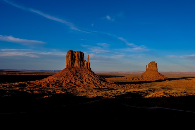 Beautiful shot of desert with dried bushes and big cliffs in the distance under a blue sky