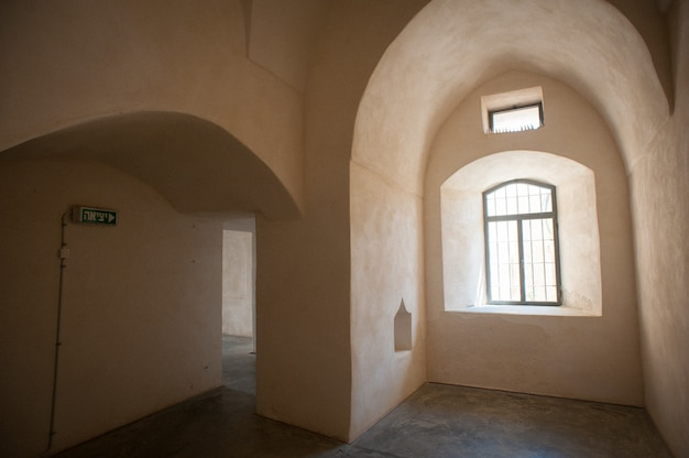 Bella ripresa di un interno di un edificio vuoto con pareti beige di finestre e un segnale di uscita