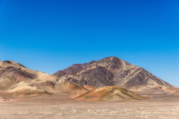 Bella ripresa di un campo vuoto con montagne in lontananza sotto un cielo blu chiaro