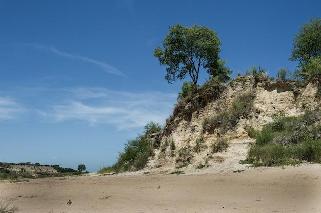 Bellissimo scatto di una spiaggia deserta con una scogliera sotto un cielo blu