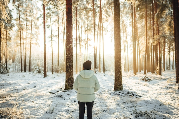 Beautiful shot of a female standing in the snowy woods