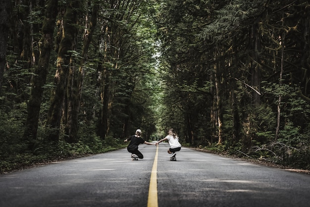 Beautiful shot of females holding hands white skating on an empty road  in the middle of forest