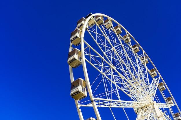 Beautiful shot of a ferris wheel on the amusement park against the blue sky