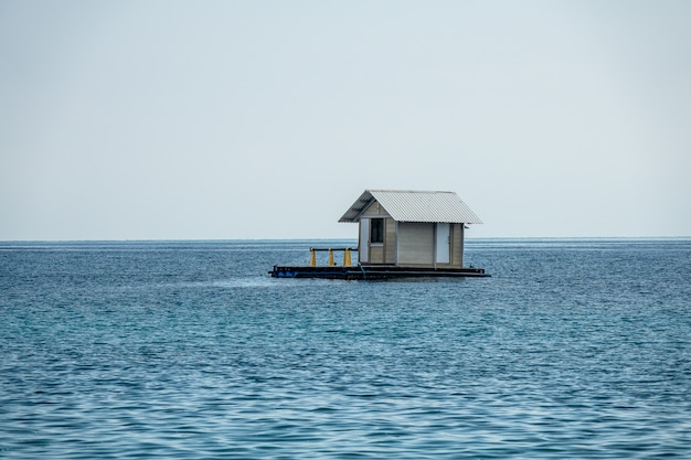 Beautiful shot of a floating house in a blue ocean with a clear white sky in the