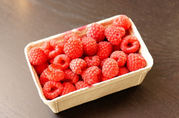 Beautiful shot of fresh raspberries in a plastic plate on the wooden table