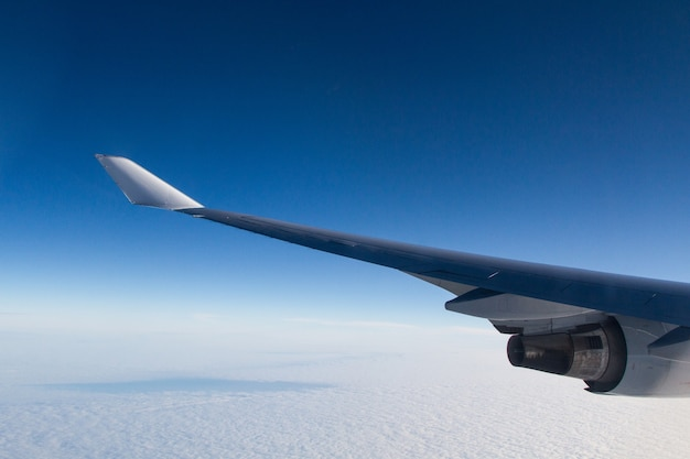 Красивый снимок из иллюминатора самолета крыльев над облаками