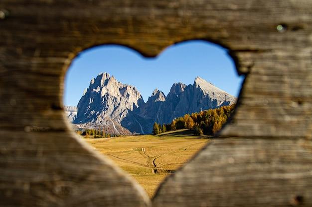Bellissimo scatto da intere montagne e alberi verdi a forma di cuore in lontananza nelle dolomiti italia