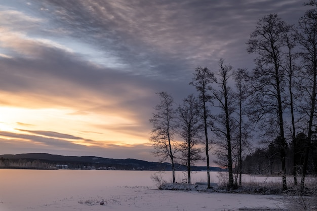 Beautiful shot of a  frozen lake with a scenery of sunset in the sky