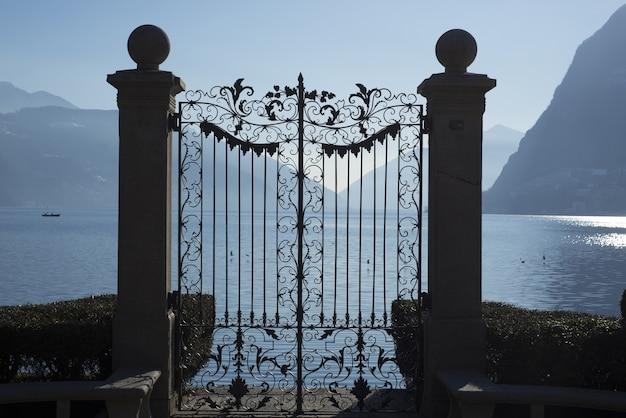 Bella ripresa di un cancello sul lago alpino di lugano con montagne in ticino, svizzera