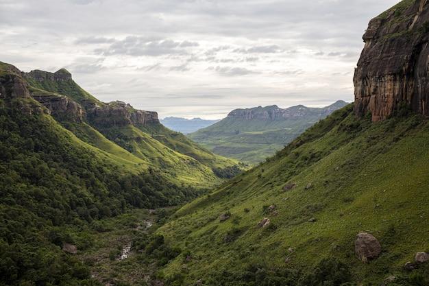 Bella ripresa di una verde vallata con alte rocce e ripide colline sotto un cielo nuvoloso grigio cupo