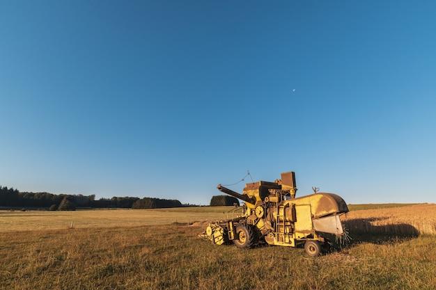 Bellissimo colpo di macchine mietitrebbia in fattoria con uno sfondo di cielo blu