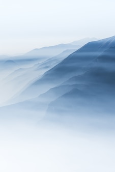 Beautiful shot of high white hilltops and mountains covered in fog