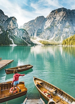 A beautiful shot of a lake with few boats with a female standing on one of them