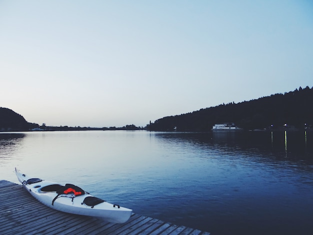 Beautiful shot of a lake with a white kayak on a brown wooden dock