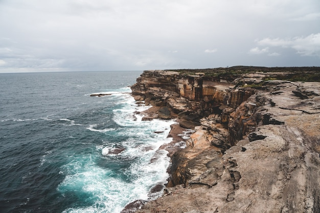 Beautiful shot of a large cliff next to blue water on a gloomy day