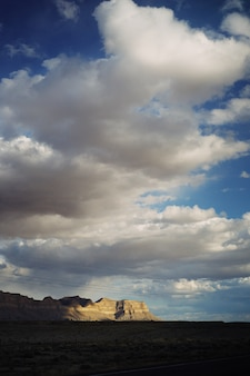Bello scatto di un grande deserto con nuvole mozzafiato e colline rocciose
