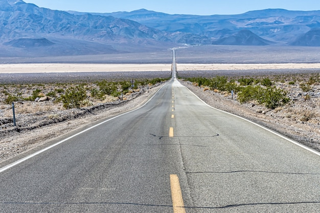 Beautiful shot of a long straight concrete road in between the desert field