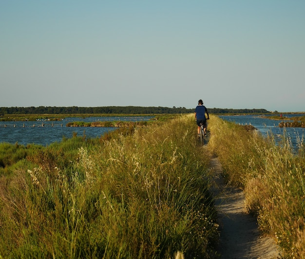 Beautiful shot of a male listening to music while riding his bicycle on a trail surrounded by water