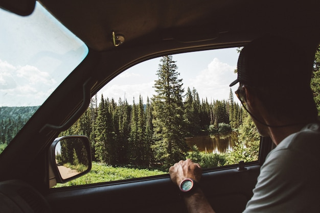 Beautiful shot of a male sitting in the car enjoying the view of pine trees near the pond