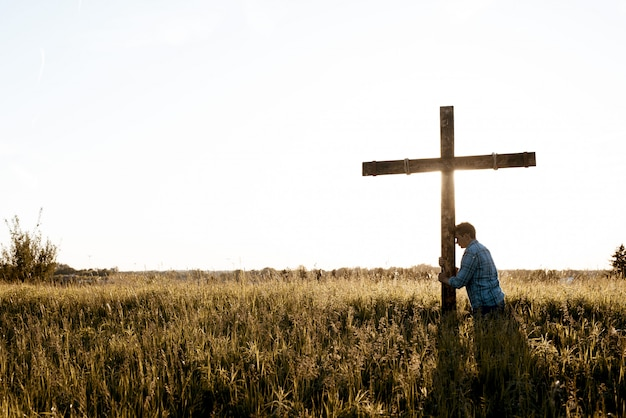 Beautiful shot of a male with his head against the wooden cross in a grassy field