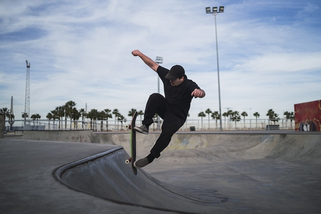 Beautiful shot of a man skateboarding in a skatepark during daytime