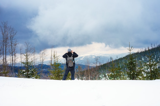 Beautiful shot of a man taking a picture of snowy forested mountains