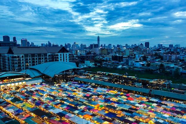 Bella ripresa di tende da mercato vicino a edifici sotto un cielo nuvoloso blu