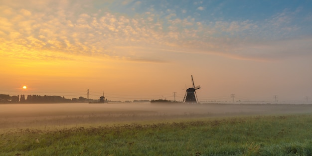 Beautiful shot of mills in the field with the sun rising in the