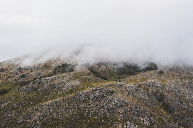 Bella ripresa di una montagna ricoperta di spesse nuvole bianche