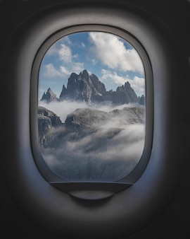 Beautiful shot of mountains and a cloudy sky from the inside of plane windows