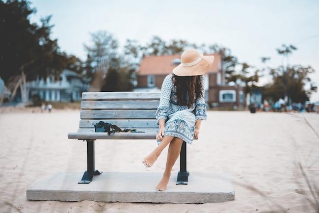 Красивая съемка босой женщины, сидя на скамейке на пляже с размытым