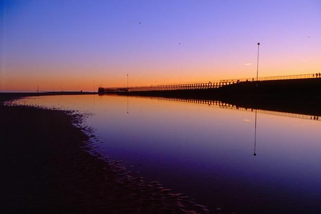夕方の空に沈む夕日の風景と海岸のビーチの美しいショット