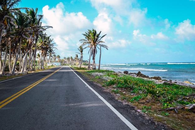 Красивый снимок пляжной дороги с пасмурным голубым небом на заднем плане