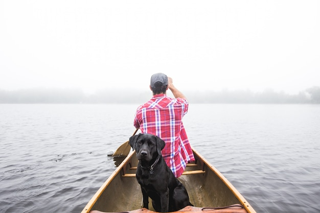 Красивый выстрел из черной собаки и самца, плывущего на маленькой лодке по водной глади