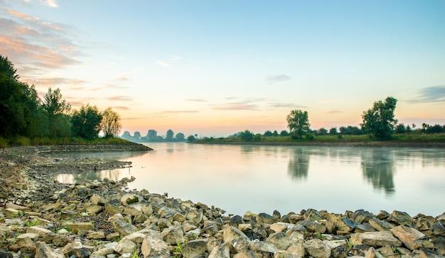 Красивый снимок спокойного озера в окружении деревьев во время заката