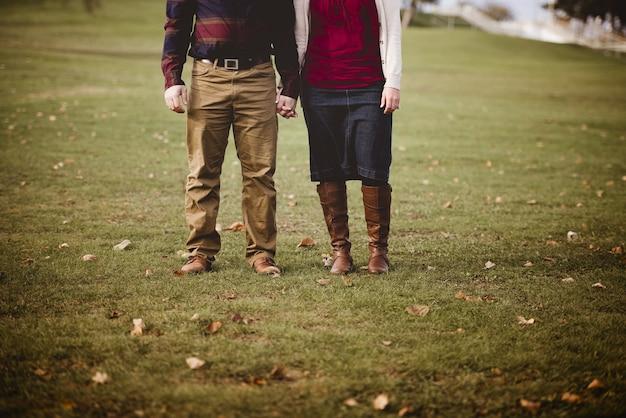 背景をぼかした写真の芝生のフィールドに立っている間手を繋いでいるカップルの美しいショット