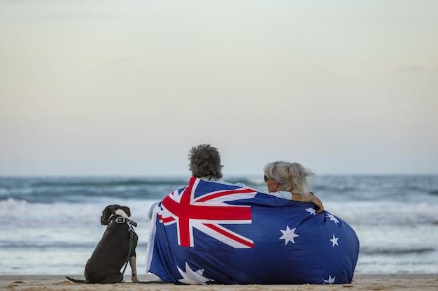 파란색 잉글리시 스태포드 강아지와 함께 해변에서 한 커플의 아름다운 사진