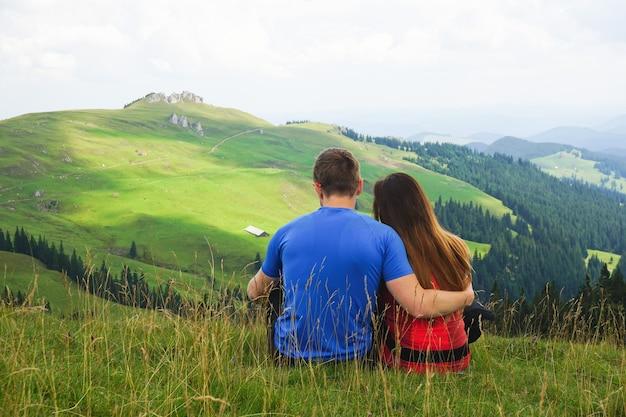 Красивый снимок пары, сидящей на горном поле