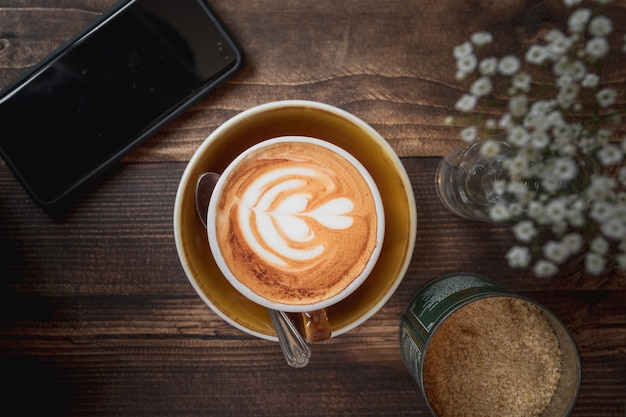 나무 테이블에 하얀 하트 패턴으로 카푸치노 한잔의 아름다운 샷