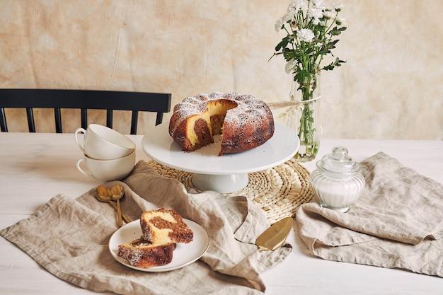 하얀 접시와 그 근처에 흰 꽃에 넣어 맛있는 링 케이크의 아름다운 샷