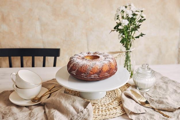 Красивый снимок вкусного кольцевого торта на белой тарелке и белый цветок рядом с ним