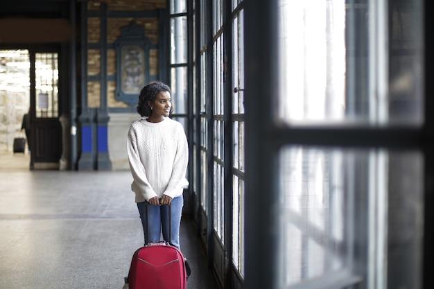 窓を見ながら赤い荷物と白い長袖の女性の美しいショット