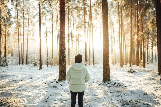 눈 덮인 숲에 서 있는 여성의 아름다운 샷