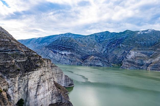 曇った青い空の下の織り目加工の石層の近くの緑の川の美しいショット