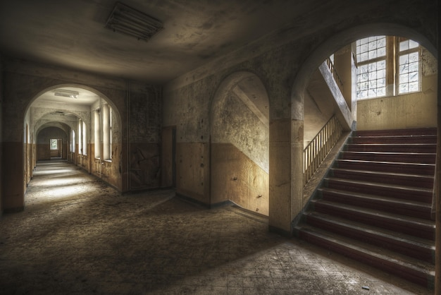 Красивый снимок коридора с лестницей и окнами в старом здании