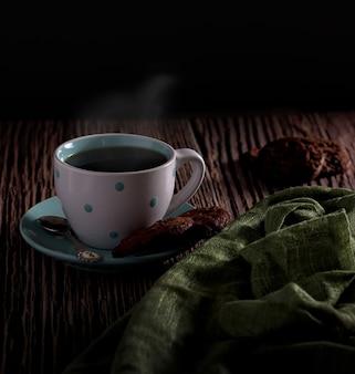 Красивый снимок горячего кофе с вкусной парой печенья на размытом фоне
